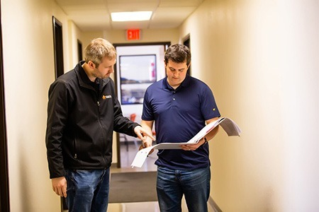 two employees going over acquired data for system auditing purposes